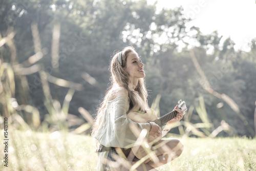 Obraz na plátne  Junge, hübsche Frau mit Gitarre auf herbstlicher WIese, Wienerw