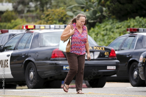 A Woman Walks Past Police Vehicles After Being Evacuated From Her