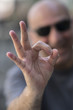 Caucasian man with sunglasses making ok sign at camera. Selective focus on foreground