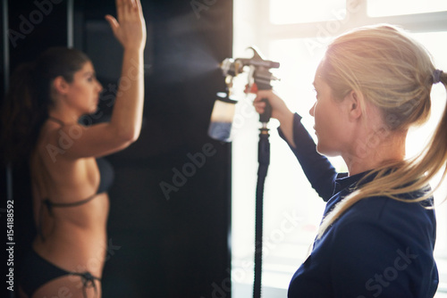 Beautician spraying tan on woman in salon Fotobehang