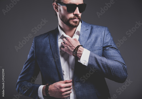 Fotografía  portrait of handsome fashion stylish hipster businessman model dressed in elegant blue suit posing on gray background in studio