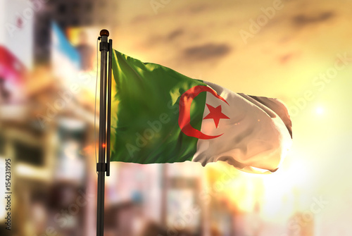 Algeria Flag Against City Blurred Background At Sunrise Backlight Canvas Print