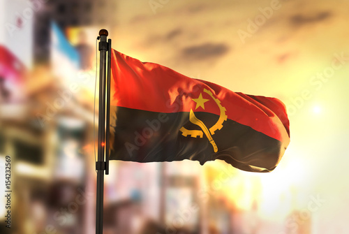 Angola Flag Against City Blurred Background At Sunrise Backlight Wallpaper Mural