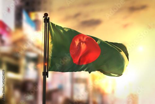 Photo Bangladesh Flag Against City Blurred Background At Sunrise Backlight