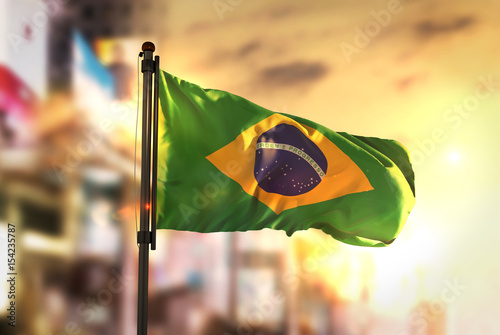 Deurstickers Brazilië Brazil Flag Against City Blurred Background At Sunrise Backlight