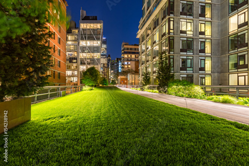 Highline promenade and lawn at twilight with city lights in the heart of Chelsea Poster