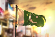 Pakistan Flag Against City Blurred Background At Sunrise Backlight
