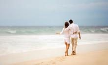 Embracing Couple Walking Along Beach