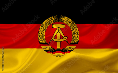 Fotomural  Flag of German Democratic Republic, with waving fabric texture