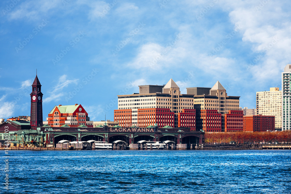 Fototapeta Hoboken, New Jersey waterfront and skyline viewed from the Hudson River. The historic Lackawanna train terminal, built 1907, is seen in the foreground.