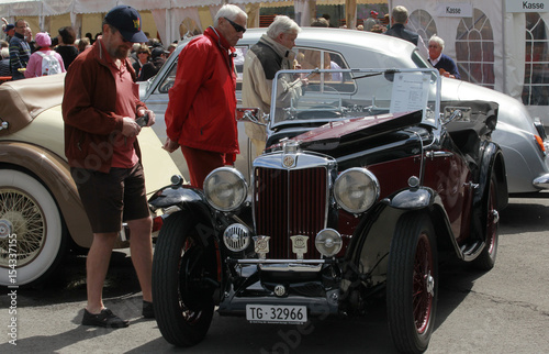 People stand beside a vintage MG sports car during the