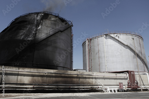 A holding tank damaged by a tank shell burns at the oil refinery in