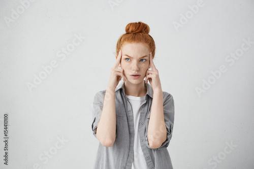 Studio shot of serious redhead young Caucasian woman holding fingers on her temp Fototapeta