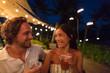 Leinwandbild Motiv Couple dating drinking at bar on night out at outdoor restaurant terrace in Hawaii vacation travel. Asian woman, man having fun together toasting mai tai drinks, hawaiian cocktail. Luxury lifestyle.