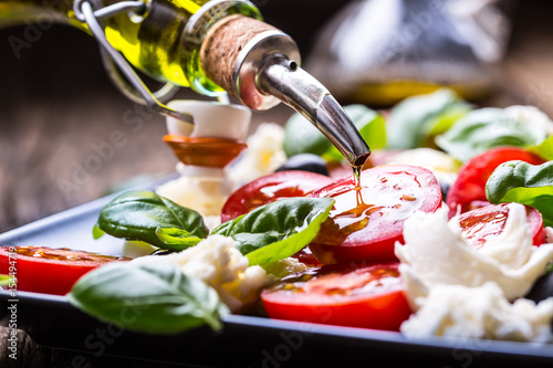 Caprese Salad.Mediterranean salad. Mozzarella cherry tomatoes basil and olive oil on old oak table. Italian cuisine.