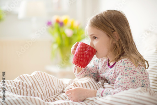 Fotografia  Pretty sick little child girl laying in bed drink tea