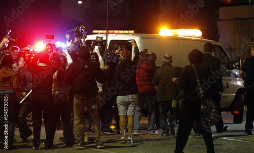 Videographers and photographers run after a Los Angeles