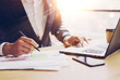 Businessman working at sunny office on laptop.Man pointing notebook keyboard and holding pen hand.Blurred background.Papaer documents on the table.Sunlight effects.