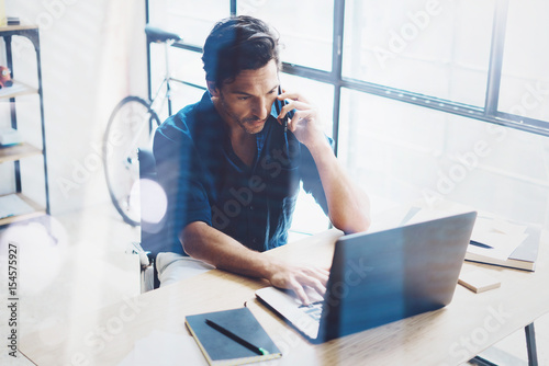 Fototapety, obrazy: Hispanic elegant businessman working contemporary notebook while sitting at the wooden table at modern loft.Man talking on his mobile phone.Blurred background. Horizontal