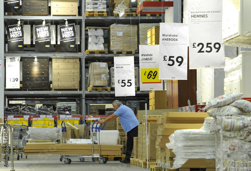 A shopper pushes goods past Ikea signs at the Wembley branch of the