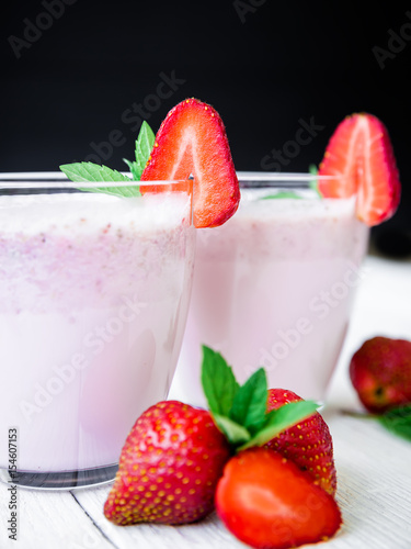 Foto op Plexiglas Milkshake Blueberry smoothie with strawberry on rustic wooden background
