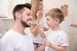 Cute little boy helping his father to brush teeth in bathroom