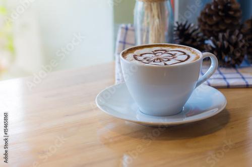 Fototapeta hot coffee with foam milk art in afternoon break. Coffee mocha on the wood desk obraz na płótnie