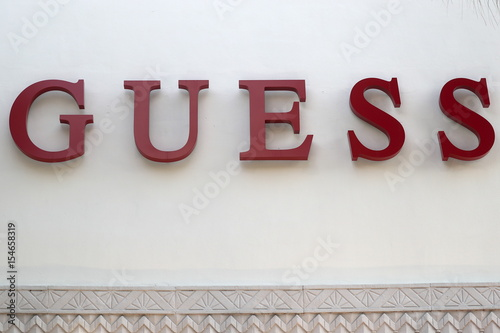 a guess store logo is pictured on a building along the lincoln road