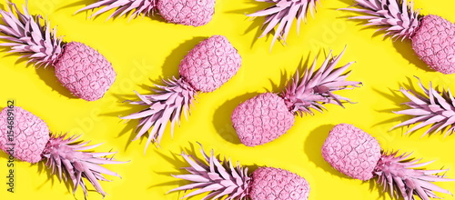 Foto  Pink painted pineapples on a vivid yellow background