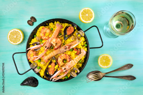 Spanish seafood paella with white wine and copyspace