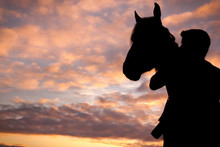 Silhouetted Man And Horse At Sunset