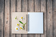 top view image of open notebook with blank pages next to chamomile flower, on old wooden table. ready for adding text mockup