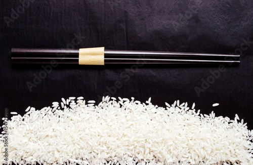 Photo  Raw white rice and chopsticks on black table