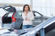 Attractive woman customer choosing a car at the dealership