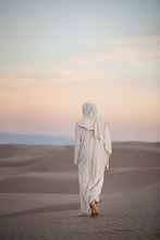 Jesus Christ Walking Through The Sand At Sunset With Light Pink And Blue Clouds, St. Anthony, Idaho