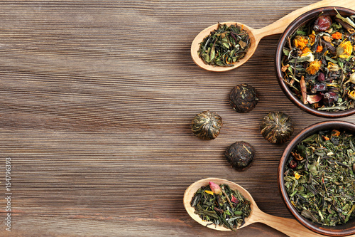 Papiers peints Herbe, epice 2 Dried tea in bowls and spoons on wooden background, top view