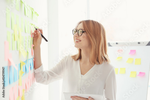 Young woman holding tablet and making notes on color stickers in office