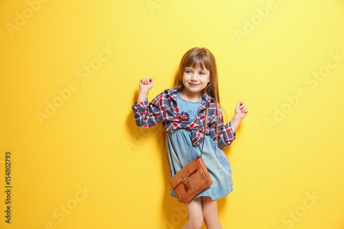 Fotografiet  Cute little girl on color background. Fashion concept