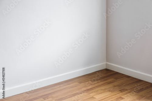 Laminated wood floor with white wall, room's corner Poster Mural XXL