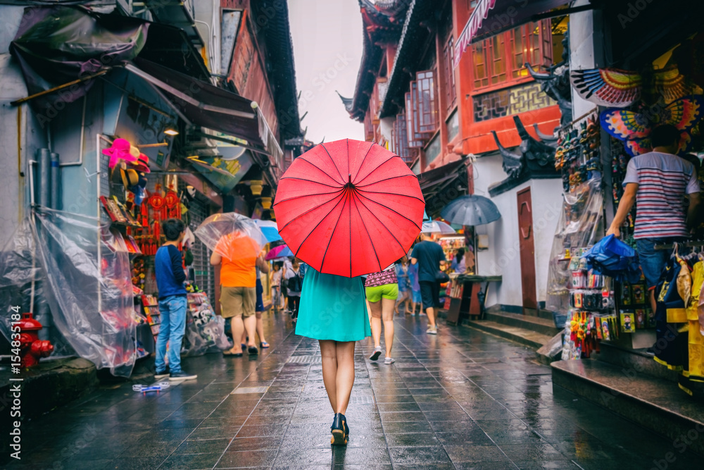 Fototapeta People woman walking in chinatown shopping street. Rainy day girl tourist under red oriental umbrella in narrow alleys on china travel in Shanghai.