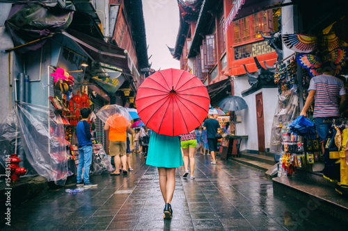 Canvas Prints Asian Famous Place People woman walking in chinatown shopping street. Rainy day girl tourist under red oriental umbrella in narrow alleys on china travel in Shanghai.