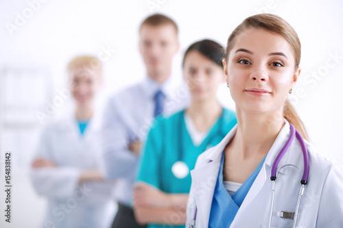 Leinwand Poster  Attractive female doctor in front of medical group