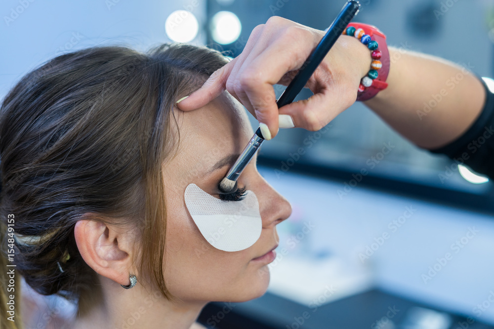 Fototapety, obrazy: Make-up artist doing makeup to beautiful young girl in the studio. The makeup artist tints the eyebrows.