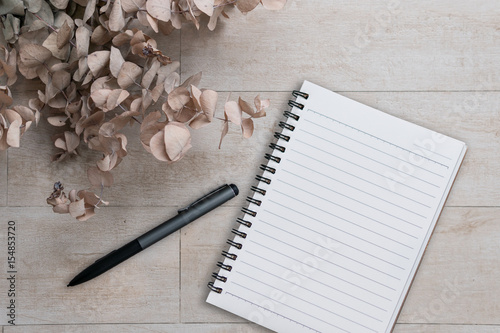 Fotografie, Tablou  Dry flowers and note book with pen on wooden background