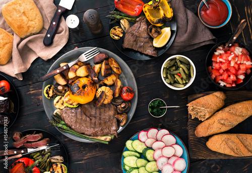 Plakat grillowany stek i grillowane warzywa na ciemny drewniany stół