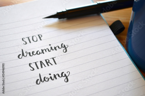 Photo STOP DREAMING START DOING hand lettered motivational quote in notebook