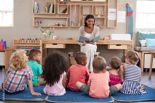 Fotografía Teacher At Montessori School Reading To Children At Story Time
