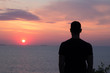 silhouette of fit young man watching wunset or sunrise in the sea or ocean