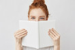 canvas print picture Portrait of ginger girl hiding behind book looking at camera.