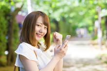 スマホを見てガッツポーズをする若い女性 緑の遊歩道